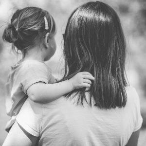 fille touche les cheveux de sa maman de dos